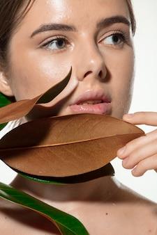 Ispirato. chiuda in su di bella giovane donna con i fogli verdi sul suo fronte sopra bianco. cosmetici e trucco, trattamenti naturali ed ecologici, cura della pelle