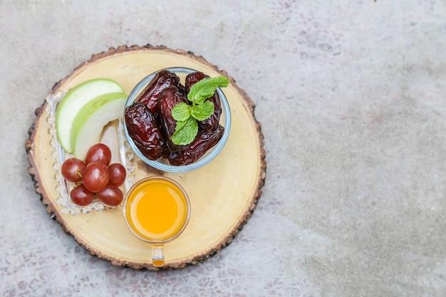 Ispirazione al ramadan con palme da datteri in una ciotola con frutta e succo d'arancia
