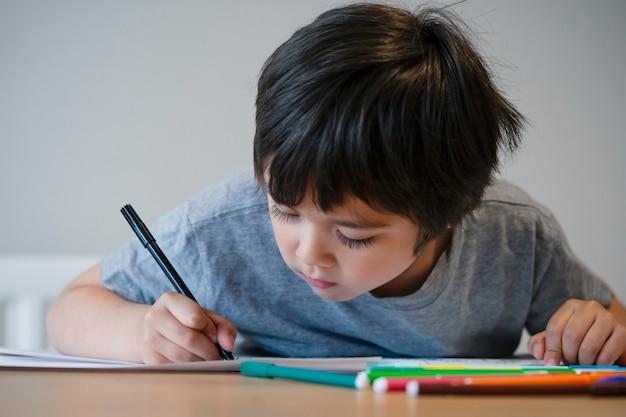 Istruisca il bambino che disegna e che colora sul libro bianco, bambino che fa a casa il lavoro a casa.