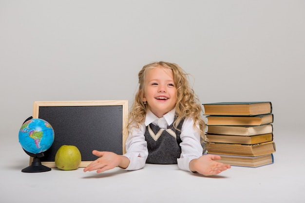Istruisca la ragazza con i libri e il tavolo da disegno in bianco su fondo bianco