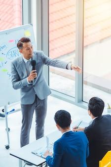 Istruttore asiatico degli uomini di affari che dà presentazione