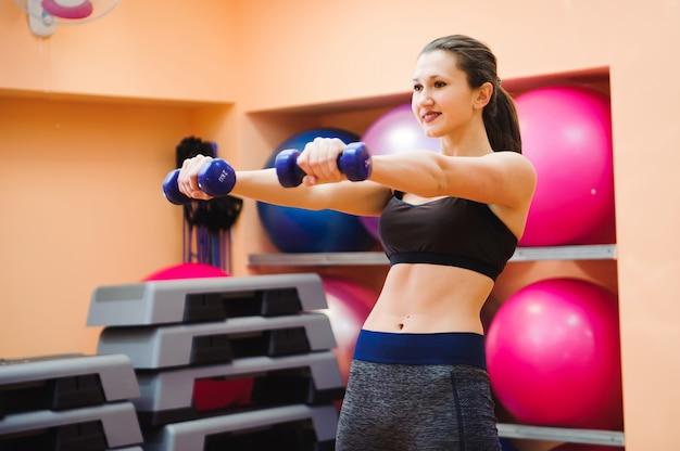 Istruttore atletico della donna che fa classe aerobica con gli stepper. sport