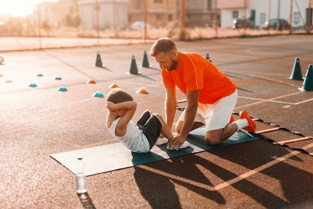 Istruttore che aiuta il bambino a fare addominali in campo al mattino.