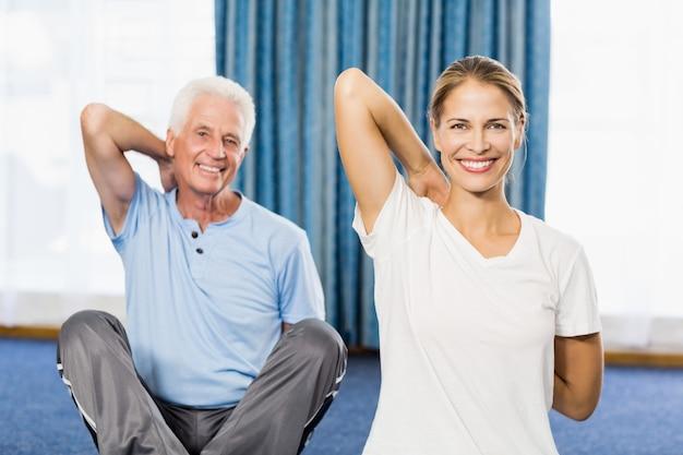 Istruttore che aiuta uomo senior con gli esercizi di sport