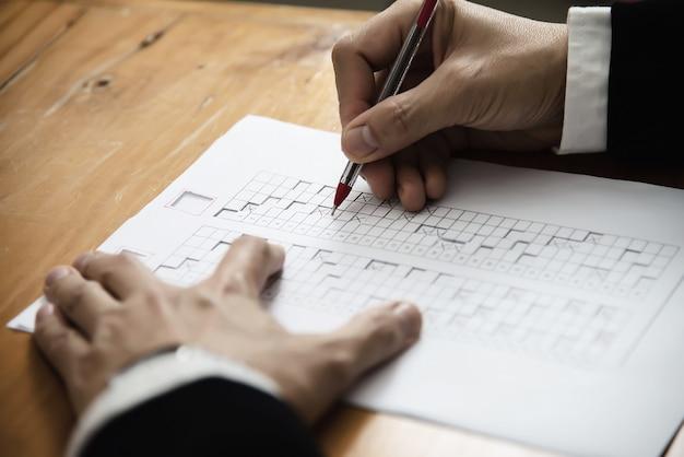 Istruttore che controlla l'esame del foglio di risposta di scelte multiple - la gente di istruzione che lavora con il concetto di prova di carta