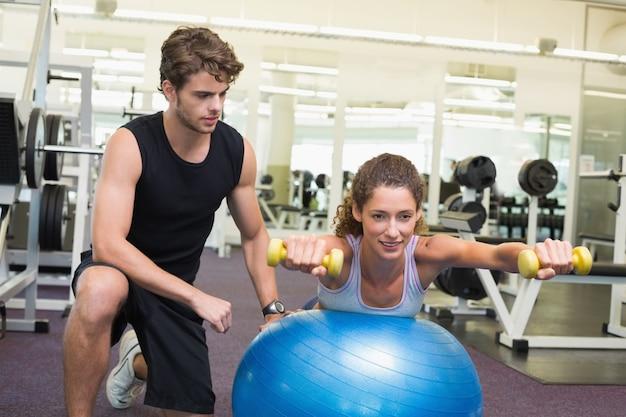 Istruttore che guarda l'equilibrio del cliente sulla palla di esercizio con i dumbbells