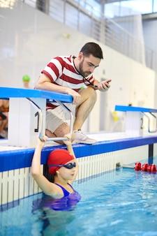 Istruttore che prepara la ragazza in piscina