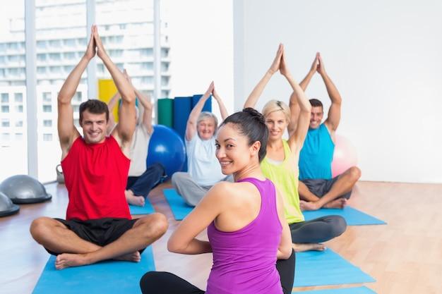 Istruttore con yoga di pratica della classe nello studio di forma fisica