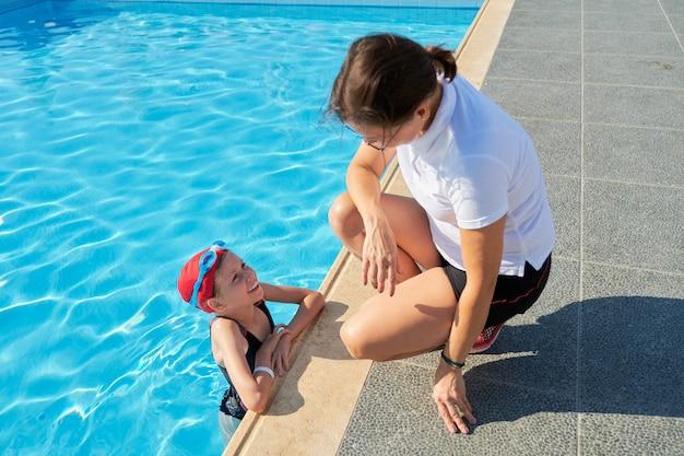 Istruttore della donna che parla con bambino della ragazza in cappello e occhiali di protezione del costume da bagno vicino allo stagno all'aperto