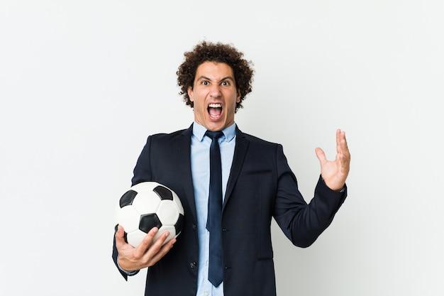 Istruttore di calcio che tiene una palla che celebra una vittoria o un successo