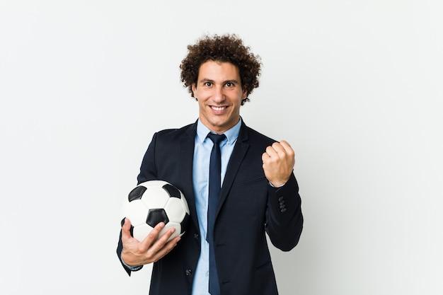 Istruttore di calcio che tiene una palla incoraggiante spensierata ed eccitata.
