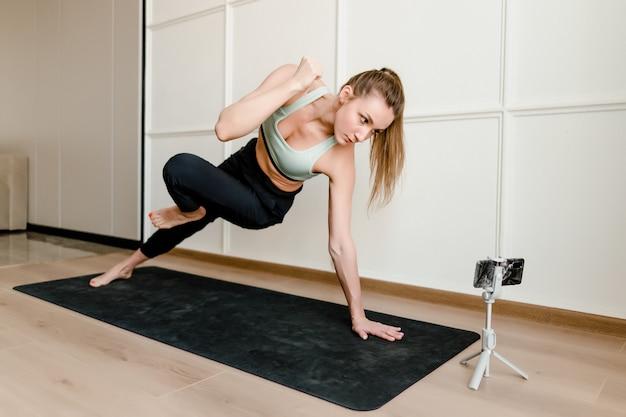 Istruttore di fitness che registra allenamento sportivo in diretta sul telefono per i clienti online a casa