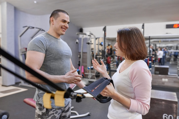 Istruttore di fitness e donna matura in palestra.