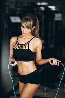 Istruttore di fitness femminile in palestra con la corda per saltare