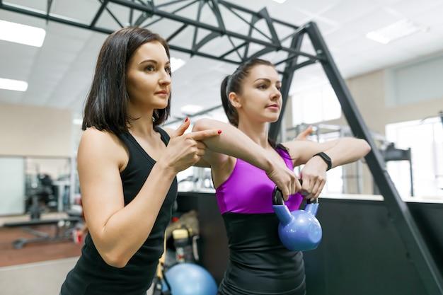 Istruttore di fitness personale che istruisce e aiuta la donna del cliente