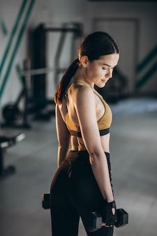 Istruttore di forma fisica della giovane donna alla palestra