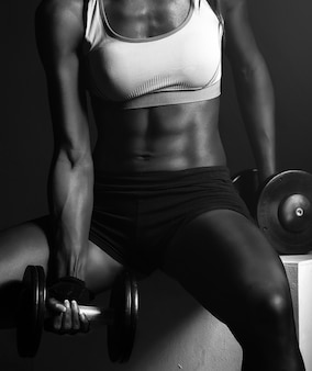Istruttore di forma fisica della ragazza dell'afroamericano con i dumbbells che fanno le esercitazioni