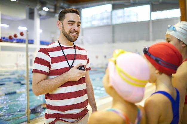 Istruttore di nuoto che insegna ai bambini a nuotare