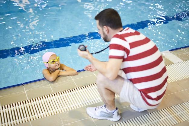Istruttore di nuoto che insegna al bambino