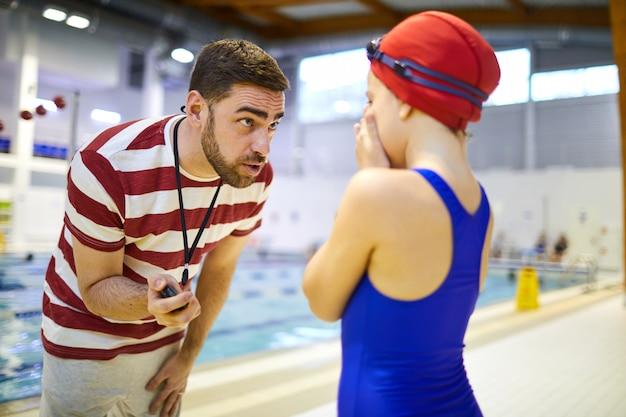 Istruttore di nuoto che parla con atleta