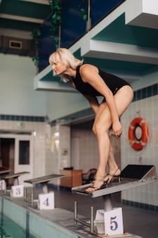 Istruttore di nuoto femminile che salta in piscina