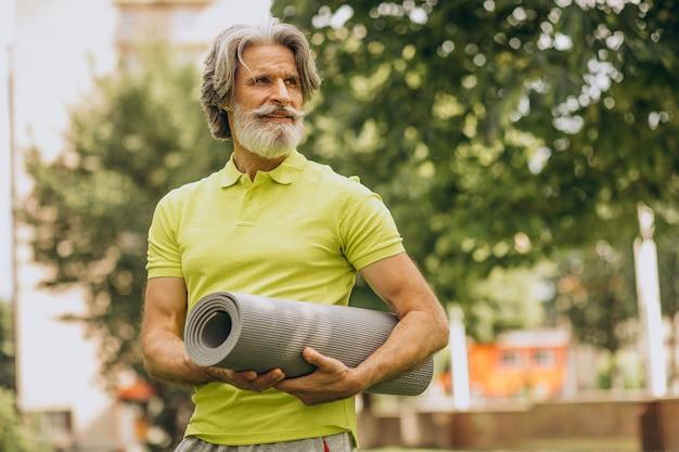 Istruttore di yoga di mezza età con tappetino nel parco