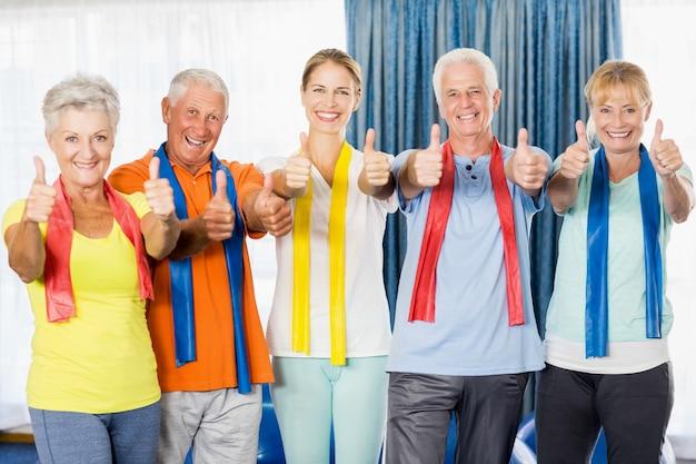 Istruttore e anziani con il pollice in alto