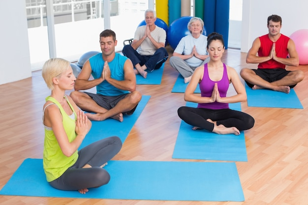 Istruttore femminile con classe meditando in palestra