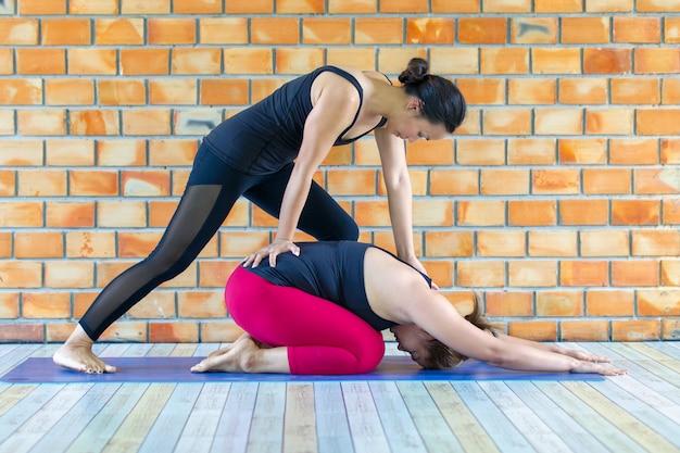 Istruttore femminile degli asiatici che aiuta giovane donna che fa yoga.