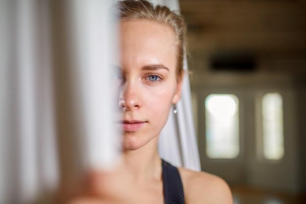 Istruttore in primo piano aereo ritratto di yoga. ragazza dei pantaloni a vita bassa con un istruttore espressivo di yoga di sguardo che posa per la macchina fotografica