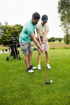 Istruttore maschio che assiste donna nell'apprendimento del golf