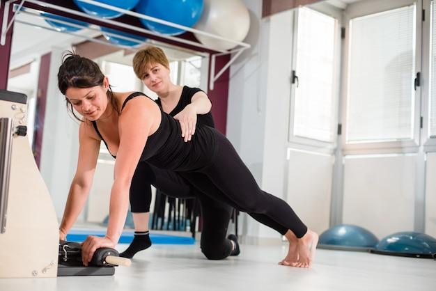 Istruttore personale che controlla giovane donna che si esercita sulla sedia combinata dei pilates di wunda