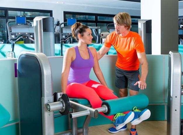 Istruttore personale della donna di allenamento di estensione della gamba della palestra
