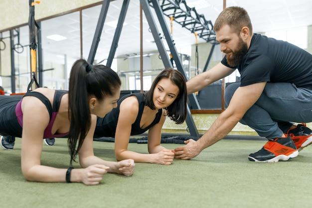 Istruttore personale di forma fisica che istruisce e che aiuta la donna del cliente