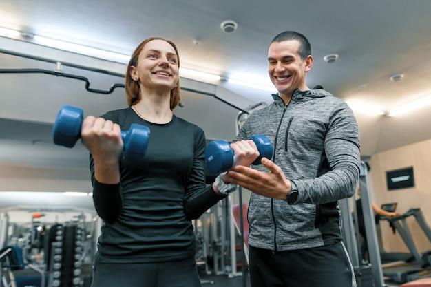 Istruttore personale maschio di forma fisica che aiuta giovane donna a fare allenamento in palestra