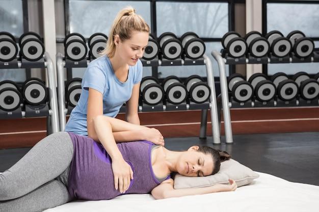 Istruttore sorridente che massaggia donna incinta alla palestra