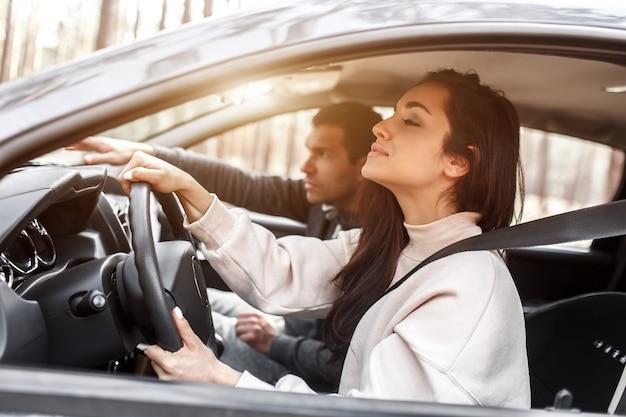 Istruzione di guida. una giovane donna impara a guidare un'auto per la prima volta. il suo istruttore o fidanzato la aiuta e le insegna