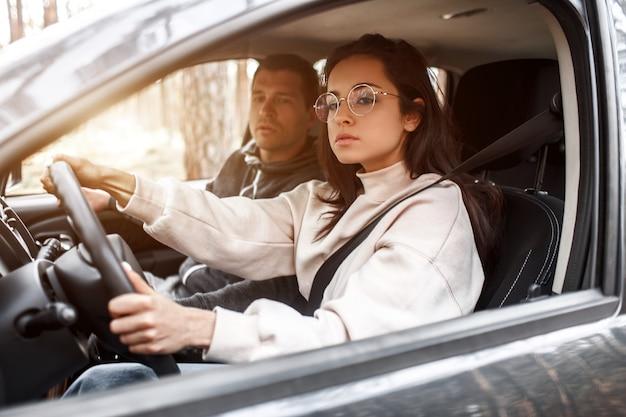 Istruzione di guida. una giovane donna impara a guidare un'auto per la prima volta