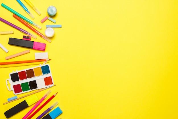 Istruzione e ritorno al concetto di scuola. rifornimenti di scuola per disegnare su uno sfondo giallo. vista dall'alto, piatta distesa.