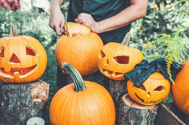Jack-o-lantern con la mano dell'uomo taglia un coperchio da una zucca.