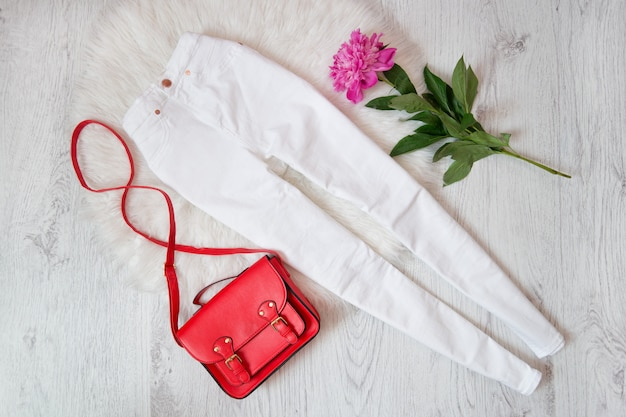 Jeans bianchi, borsa rossa e peonia