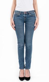 Jeans d'uso della donna e mezzo busto di vista frontale stanti della maglietta bianca isolati su fondo bianco