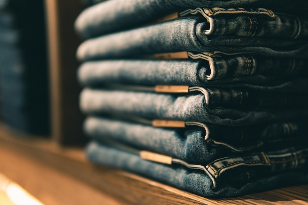 Jeans impilati con vita multipla su mensole o armadi e fuoco selettivo.