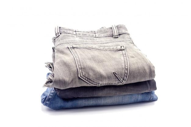 Jeans impilati su uno sfondo bianco