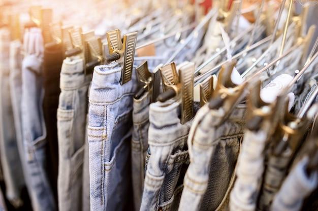 Jeans in vendita appesi nel mercato delle pulci