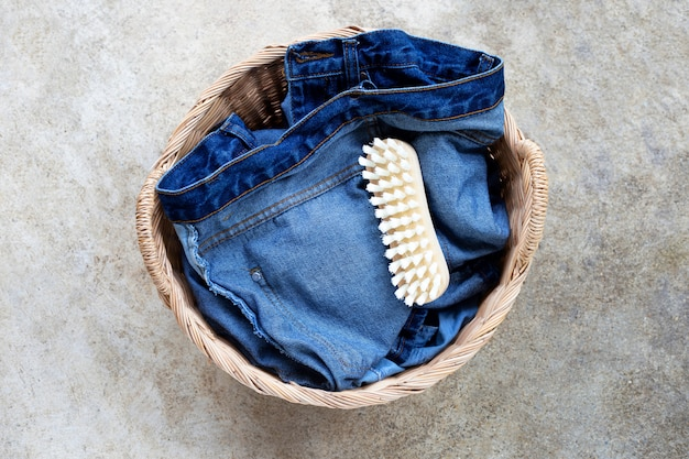 Jeans nel cesto della biancheria sul pavimento di cemento.