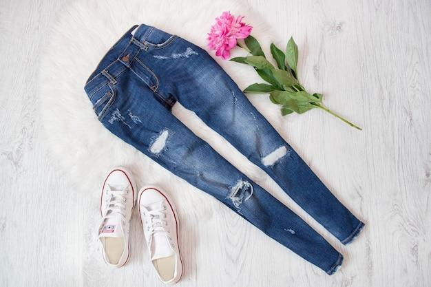 Jeans strappati, scarpe da ginnastica bianche e peonia rosa. tavolo bianco concetto alla moda