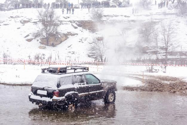 Jeep rotta nel mezzo di un fiume con fumo