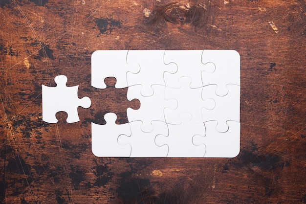 Jigsaw puzzle con pezzo mancante su legno vecchio
