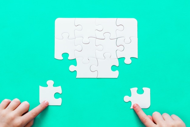 Jigsaw puzzle con pezzo mancante su sfondo di menta mano di persone
